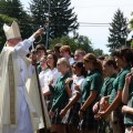 Bishop sprinkling students during outdoor ceremony